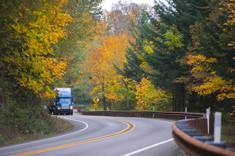 truck driving by trees with fall colors